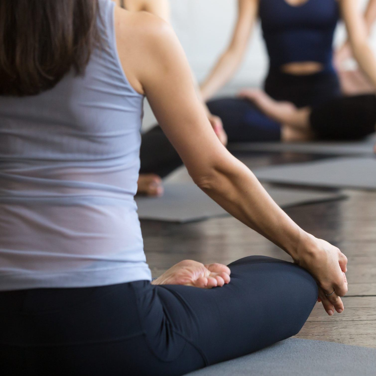 Group of young sporty people practicing yoga lesson with instructor, sitting in easy pose, Lotus exercise, working out, indoor close up, studio, students training in club. Rear view